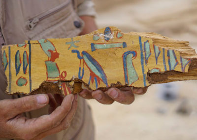 Fragmento de ataúd hallado entre los linos de la momia desmembrada que asoma por la boca un pozo.