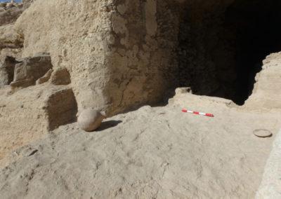 Entrada a la tumba asociada al jardín, con un plato y una vasija apoyados sobre un suelo de mortero.