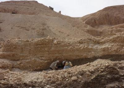 Javier y el mudir buscan pigmentos en los estratos del suelo rocoso.