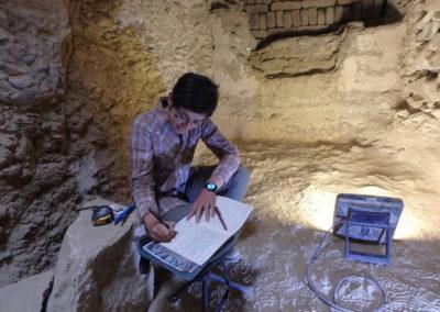 Angie revisa el croquis de la estratigrafía del cierre de la tumba grande.