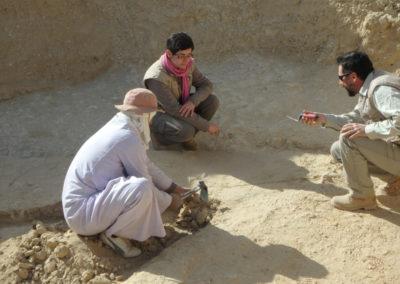 Angie, David y Gamal discuten sobre cómo continuar excavando y dónde dejar un testigo de la estratigrafía.