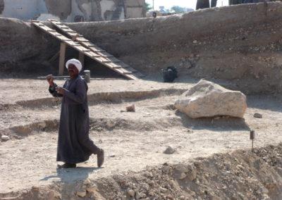 Yuma se prepara para romper o mover una gran piedra en la zona de excavación frente al jardín.