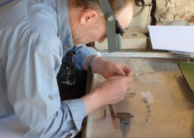 Neal comienza a estudiar los esqueletos de las momias de musarañas.