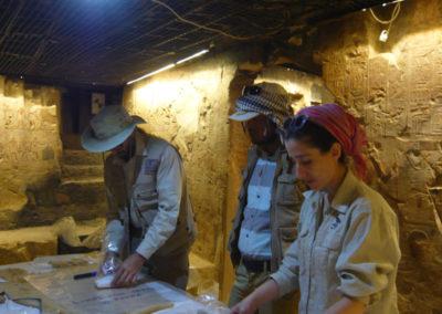 Curro, el inspector Ahmed y Gudelia revisan un conjunto de linos con inscripción.