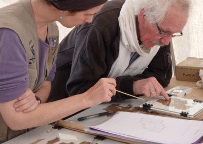 Lucía y el profesor Rob Demarée revisan la lectura de unos fragmentos de papiro.