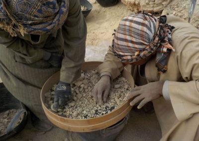 Ibrahím y Yasín criban la tierra extraída de la tumba que excava Carlos.