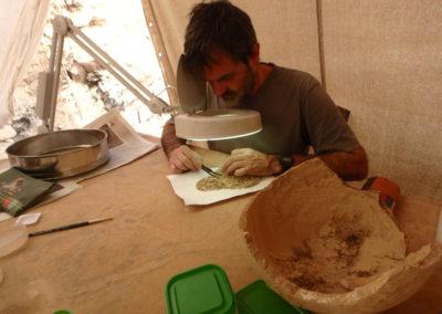 Guillem revisa el contenido de una vasija procedente de la excavación de Carlos dentro de la gran tumba.