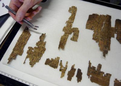 Bridget va poco a poco colocando y pegando trocitos de papiro con el Libro de los Muertos de la señora de la casa Tanedjem.