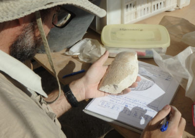 Curro estudia la inscripción grabada en un fragmento de vaso canopo hallado hace unos días por Kristian.